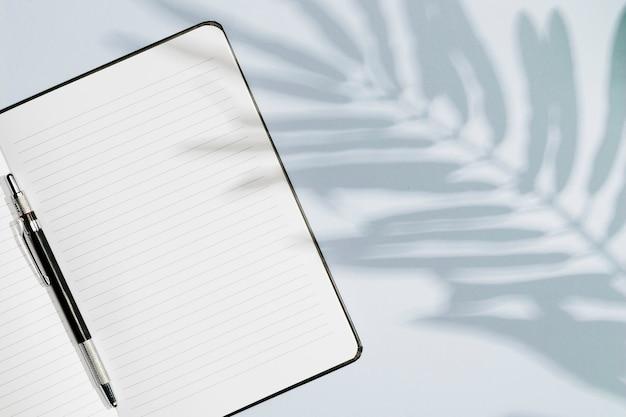 Kopieer ruimte notebook met bladeren schaduw