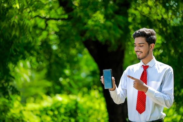 Kopieer ruimte op zijn slimme telefoon. zelfverzekerde jonge indiase man met zijn slimme telefoon