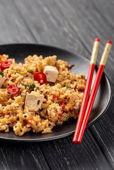 Kopieer ruimte rijst met groenten op plaat en eetstokjes met kopie ruimte