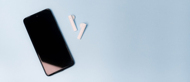Kopieer ruimte telefoon en draadloze koptelefoon. modern ontwerp. elektronica. selecteer een koptelefoon voor je telefoon. moderne gadgets. witte draadloze koptelefoon. bluetooth koptelefoon. kopieer ruimte