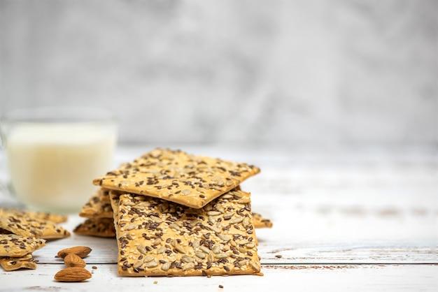 Kopje amandelmelk en stapel volkoren koekjes op licht