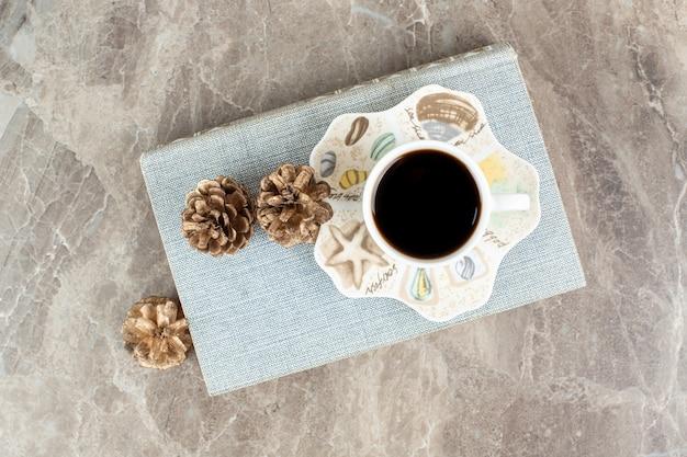 Kopje aromatische koffie bovenop een boek met dennenappels
