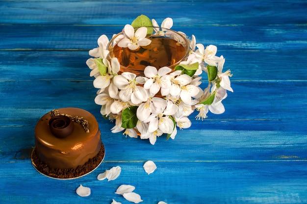 Kopje bloementhee, versierd met appelbloesems en prachtige chocoladecake.