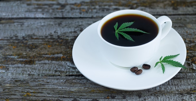 Kopje cannabis koffie met hennepbladeren en gebrande koffiebonen op houten tafel