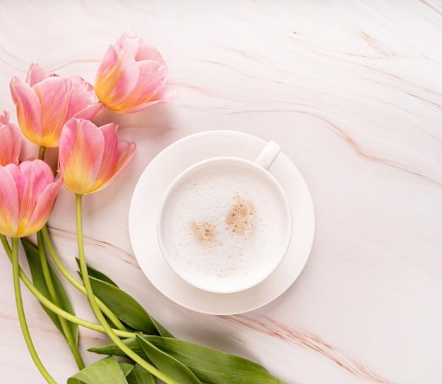 Kopje cappuccino en roze tulpen bovenaanzicht op marmeren achtergrond