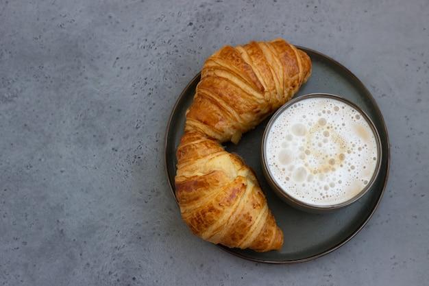 Kopje cappuccino en twee verse croissants
