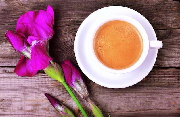 Kopje cappuccino en violet bloeiende iris