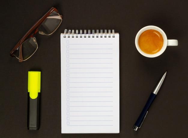 Kopje cappuccino, glazen, marker, pen en notebook om te schrijven. uitzicht van boven.