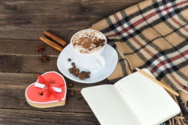 Kopje cappuccino, hartvormige koekjes breedte bericht, notebook en geruite plaid op een bruin houten tafel