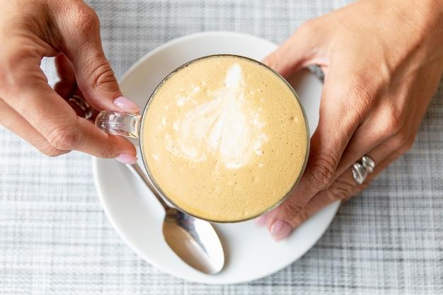Kopje cappuccino koffie in vrouwelijke handen aan een tafel in een café. bovenaanzicht.