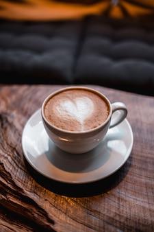 Kopje cappuccino met een hartje erop op tafel