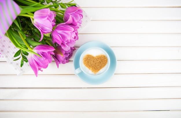 Kopje cappuccino met een hartvormig symbool en paarse tulpen op een houten ondergrond