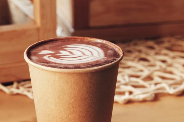Kopje cappuccino met een patroon op een tafel in een café