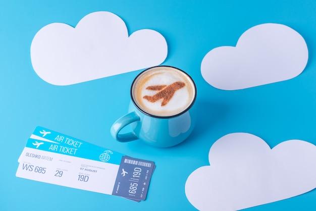 Kopje cappuccino met een vliegtuig op het schuim en kaartjes