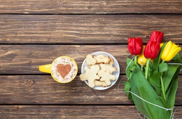 Kopje cappuccino met hartvorm en boeket tulpen met koekjes