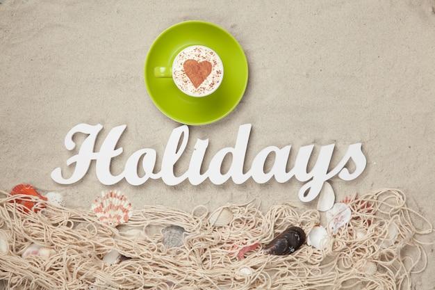 Kopje cappuccino met hartvorm symbool en woord vakantie met net en schelpen op zand