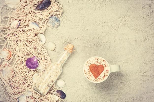 Kopje cappuccino met hartvorm symbool, fles en net met schelpen op zand