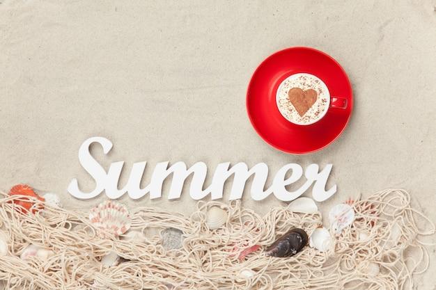 Kopje cappuccino met hartvorm symbool, woord zomer en net met schelpen op zand