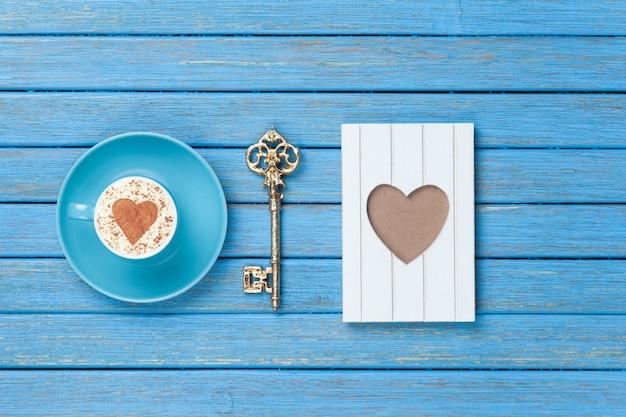 Kopje cappuccino met het symbool van de hartvorm, sleutel en fotoframe op blauwe houten.