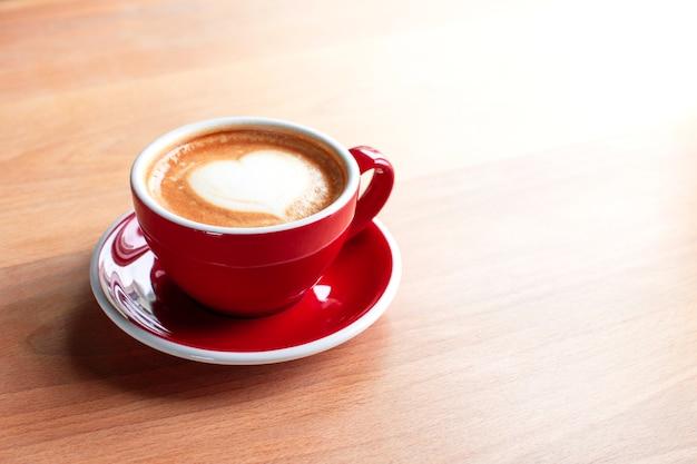 Kopje cappuccino met latte art op een houten achtergrond