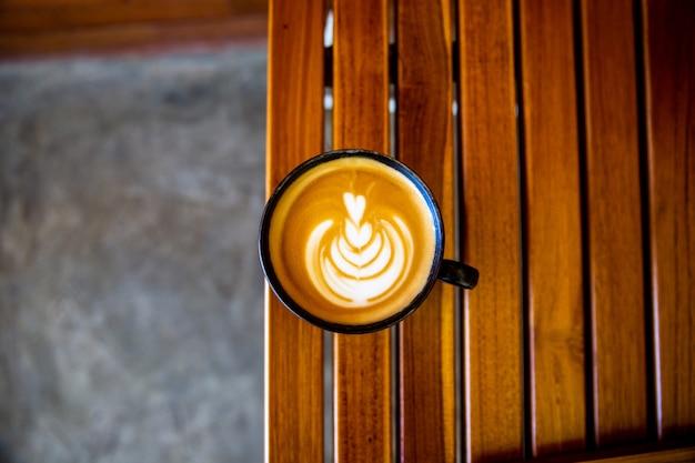 Kopje cappuccino met latte art op houten ondergrond. mooi schuim, houten bureau en bakstenen muur.