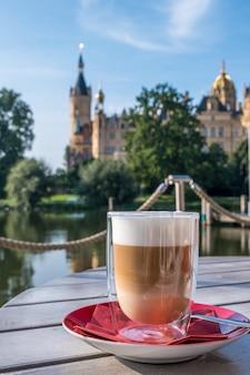 Kopje cappuccino op een terrasje of restaurant op een zomerse dag met op de achtergrond een prachtig kasteel in schwerin.