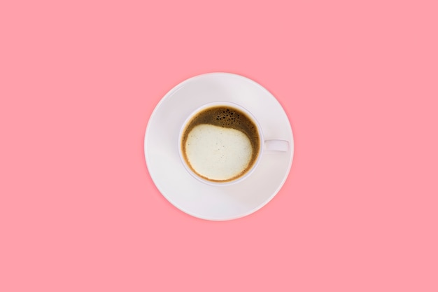 Kopje cappuccino op een witte schotel op een roze achtergrond. bovenaanzicht, plat leggen, kopie ruimte