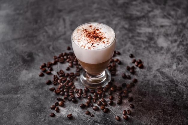 Kopje cappuccino op zwarte ondergrond. gebrande koffiebonen met warme melk, koffie en cacaopoeder met kopie ruimte