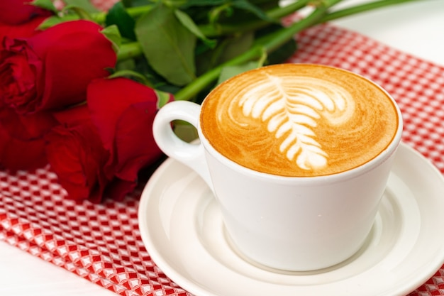Kopje cappucino met kunst en boeket rozen op houten tafel
