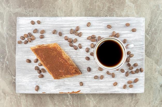 Kopje donkere koffie met bonen en gebak op een houten bord