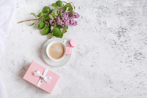 Kopje een takje lila en een roze geschenkdoos