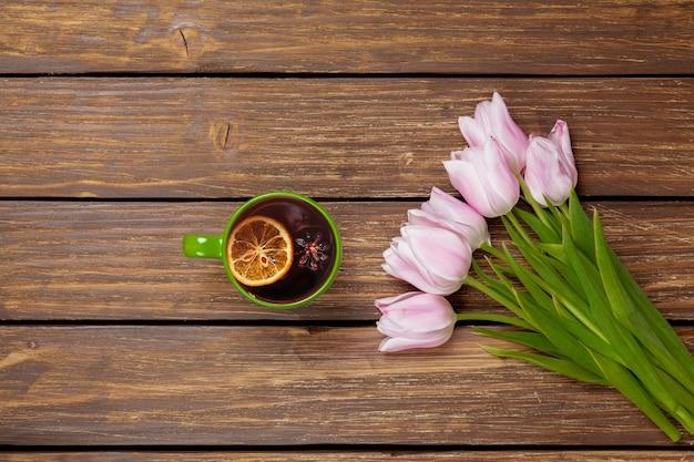 Kopje engelse thee met de lentetulpen op hout