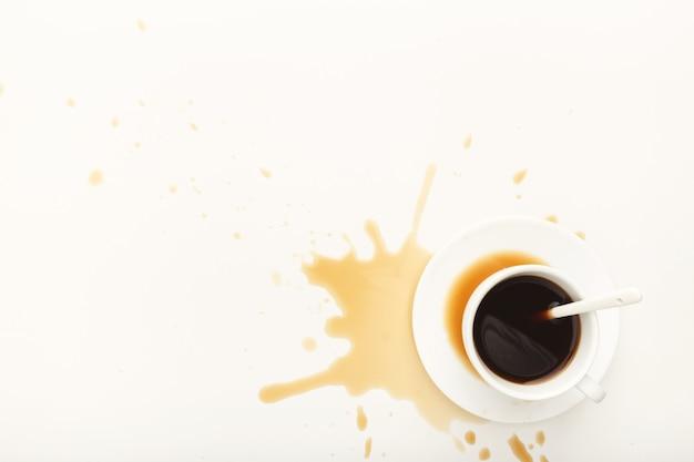 Kopje espresso en koffie gemorst op een witte geïsoleerde achtergrond, bovenaanzicht. mockup voor het ontwerp van grunge-advertenties, kopieer ruimte
