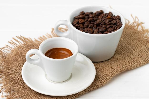 Kopje espresso koffie en koffiebonen op witte ondergrond