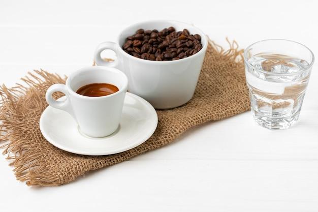 Kopje espresso met glas water op witte tafel