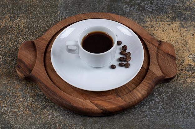 Kopje espresso met koffiebonen op een houten bord.