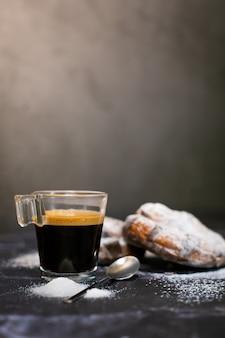 Kopje espresso met twee chocoladecroissants en poedersuiker