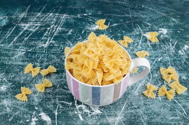 Kopje farfalle pasta op blauwe ruimte.