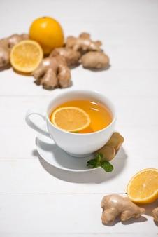 Kopje gemberthee met citroen en honing op een witte houten achtergrond.