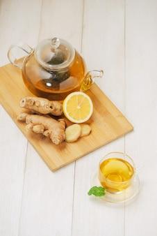 Kopje gemberthee met citroen en honing op witte houten achtergrond.