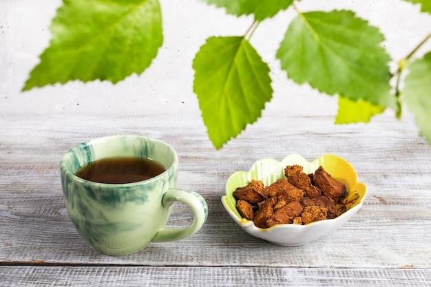 Kopje genezende drank van chaga van de berkpaddestoel op houten lijst met groene hierboven berkbladeren.