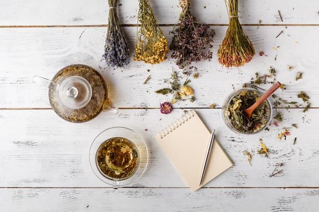 Kopje gezonde thee, honing, geneeskrachtige kruiden, kruidenthee assortiment en bessen op tafel. bovenaanzicht kruidenmedicijn.
