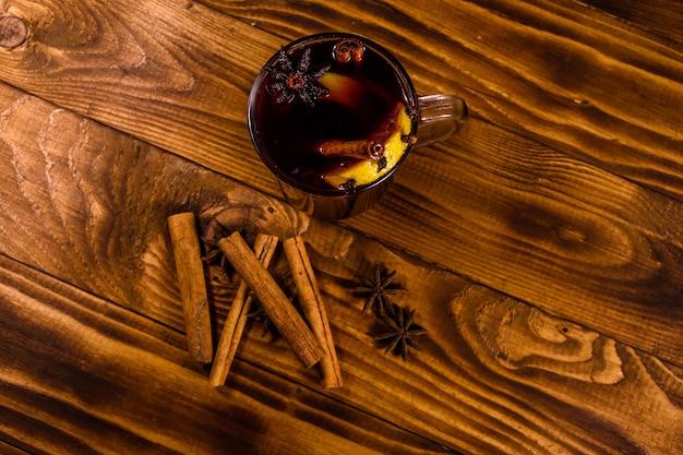 Kopje glühwein met kaneel op rustieke houten tafel. bovenaanzicht