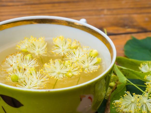 Kopje groene thee en linden op houten achtergrond, nuttige linden bloemen volksgeneeskunde concept