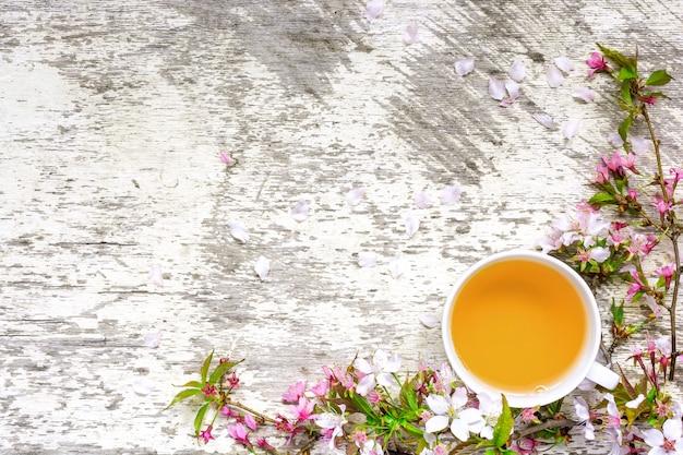 Kopje groene thee en takken van bloeiende sakura en kersen