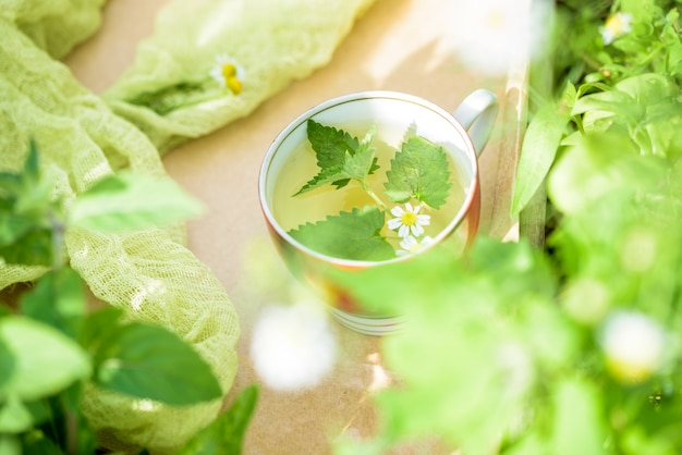 Kopje groene thee met een muntblad, bloemen, in de tuin.