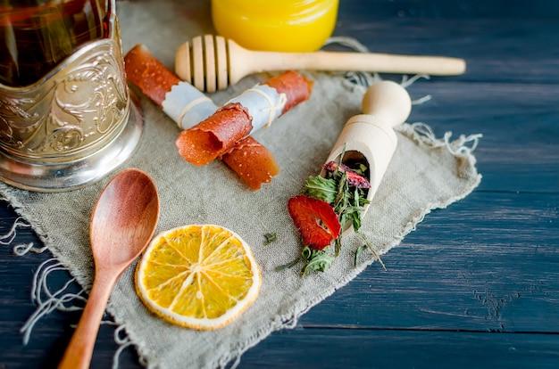 Kopje groene thee met munt, schijfje citroen, broodje droog fruit en muntblaadjes met aardbei