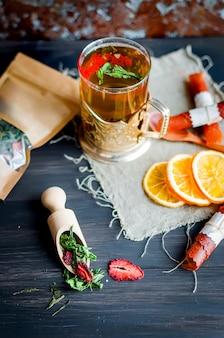 Kopje groene thee met munt, schijfje citroen, droog fruit roll en thee muntblaadjes met aardbei in een houten lepel op houten achtergrond, kopieer ruimte