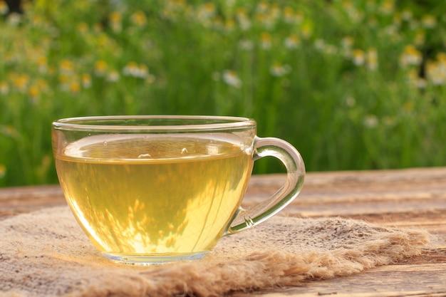 Kopje groene thee met witte kamille bloemen op houten planken met groene natuurlijke achtergrond.