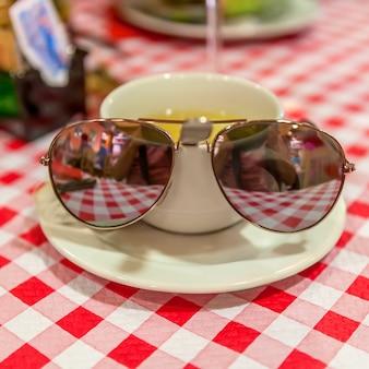 Kopje groene thee op een geruit tafelkleed en zonnebril